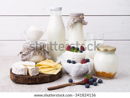 Assorted milk products for breakfast and healthy life - milk, yogurt, cheese, Camembert, home made cream cheese with berries, kefir, sour cream - stock photo