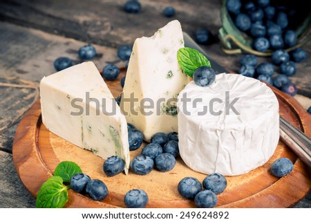 Assorted moldy cheeses and blueberries on wooden board with retro filter - stock photo