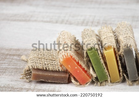 Assorted natural soaps on vintage wood. - stock photo