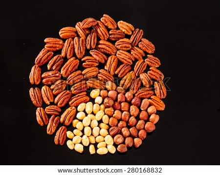 Assorted nuts (Pecan, Hazelnuts and Roasted Salted Peanuts) in a circle form on a black background - stock photo