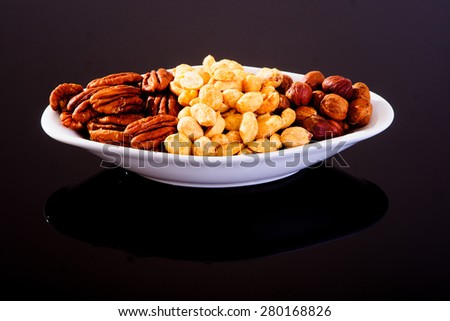 Assorted nuts (Pecan, Hazelnuts and Roasted Salted Peanuts) in a white plate on a black background - stock photo