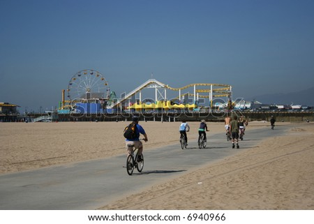 assorted people moving along cycle lane towards Santa Monica pier - stock photo