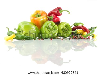 Assorted peppers bell, cayenne, pepper grains and it's reflection on a white background - stock photo