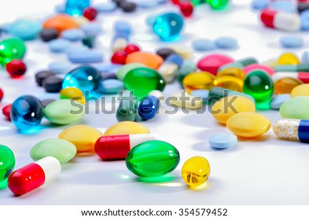 assorted pharmaceutical capsules and medication in different colors denoting different drugs and antibiotics in a health care concept - stock photo