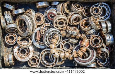 Assorted pile of ball bearing wheels in different sizes creates a retro themed industrial background. Toned image in color. - stock photo