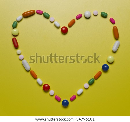 Assorted pills creating heart shape - stock photo