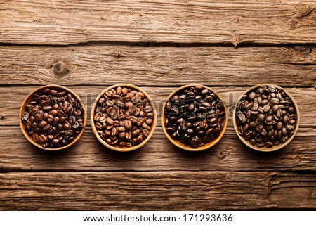 Assorted raw and roasted coffee beans in small individual containers on a rustic, weathered textured driftwood background, overhead view with copyspace - stock photo