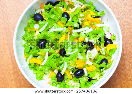 Assorted salad of green leaf lettuce with squid and black olives - stock photo
