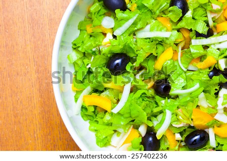 Assorted salad of green leaf lettuce with squid and black olives, close up - stock photo