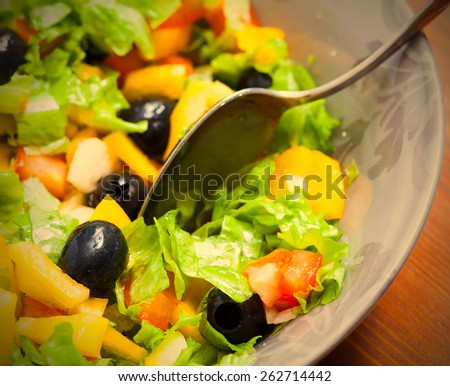 Assorted salad of green leaf lettuce with squid and black olives in bowl, close up. instahram image style - stock photo
