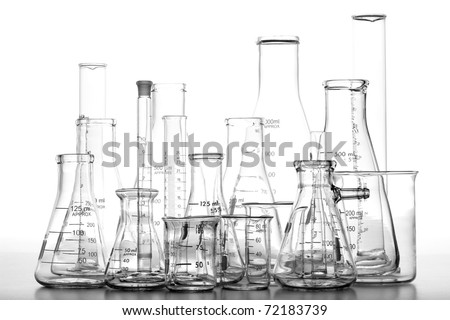 Assorted science laboratory glassware chemistry equipment featuring glass beakers with graduated scientific cylinders and conical Erlenmeyer flasks in a science research lab over white - stock photo