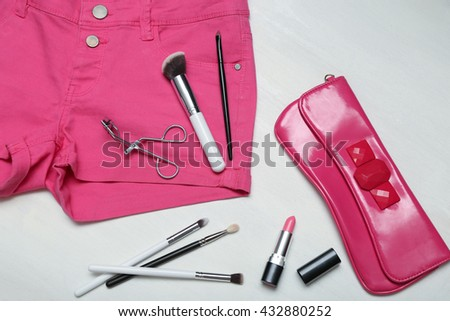Assorted set of make up brushes and tools on pink jeans shorts,  clutch on white wooden background - stock photo