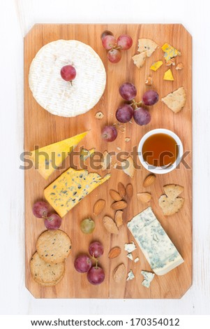 assorted soft cheeses, grapes, nuts and honey on wooden board, top view, vertical - stock photo