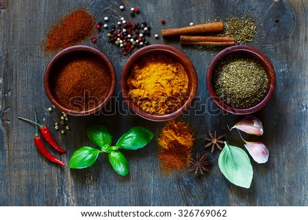 Assorted spices and herbs over dark old wood. Food and cuisine ingredients. Cooking background. - stock photo