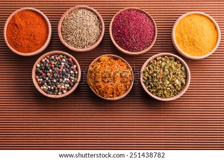 assorted spices in a wooden bowl on a brown background