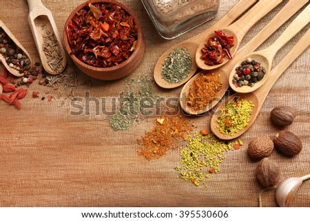 Assorted spices in spoons on wooden table, top view
