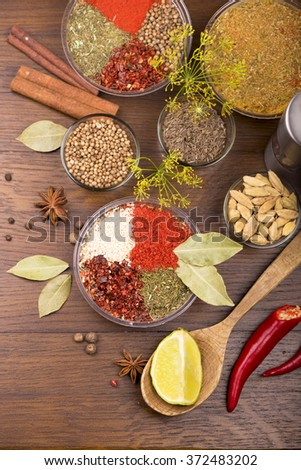 Assorted spices on wooden background  - stock photo