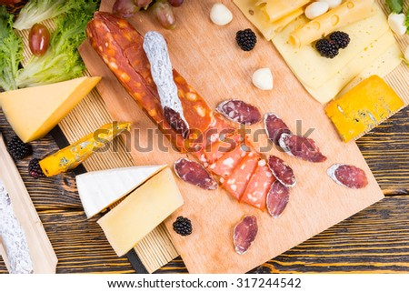 Assorted spicy cold meat with assorted cheeses arranged on a buffet table on a wooden cheese board garnished with blackberries and olives, overhead view - stock photo