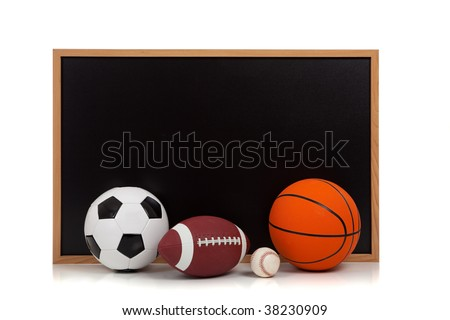 Assorted sports balls including american football, soccer ball, baseball and basketball with a chalkboard background - stock photo