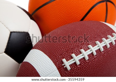 Assorted sports equipment on white including a basketball, a soccer ball, and an American Football - stock photo