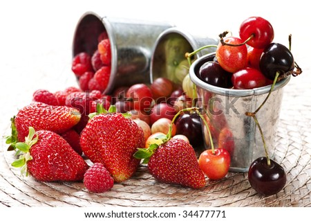 Assorted summer fruits and berries in metal pails - stock photo