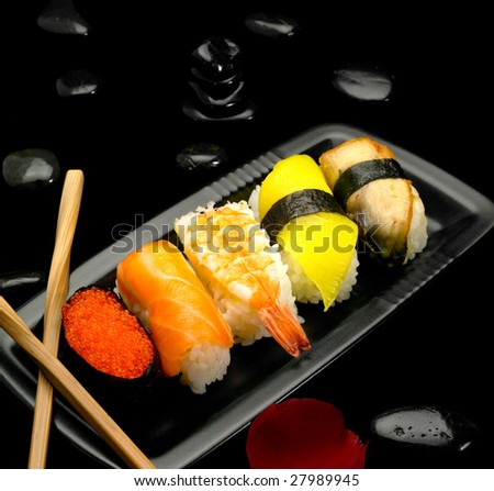 assorted sushi plate on black pebbles over black background - stock photo