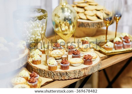 Assorted tasty finger food on wooden plate at wedding reception - stock photo