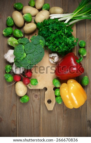 Assorted vegetables and cutting board on rustic wooden background. Top view point. - stock photo