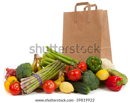 Assorted vegetables and fruits including asparagus, celery, tomatoes, peppers, bananas, lemons, cauliflower, cherry tomatoes, broccoli, cucumber and squash with a grocery sack on a white background - stock photo