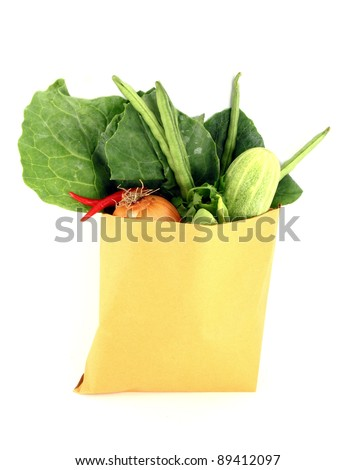 Assorted vegetables in brown bag isolated over white background - stock photo