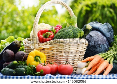 Assorted vegetables in wicker basket in the garden