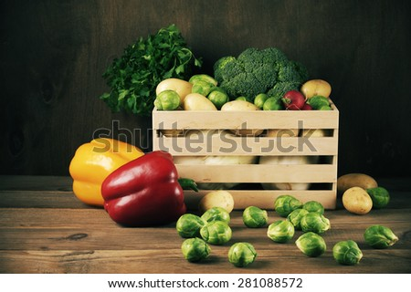 Assorted vegetables in wood box on dark rustic wooden background.  - stock photo