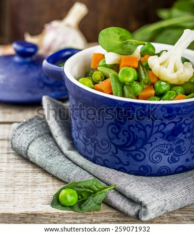 Assorted vegetables with spinach leaves in a blue ceramic pot on a wooden background. selective Focus - stock photo