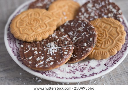 Assorted wheat cookies with chocolate ganache and freshly shredded coconut on a dessert plate, selective focus - stock photo