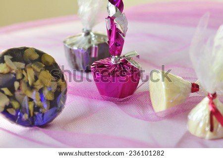 Assorted white chocolate in shiny wrapper on a colorful background - stock photo