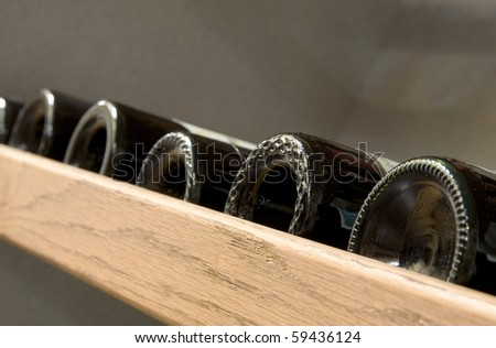 Assorted wine bottles on a shelf. - stock photo