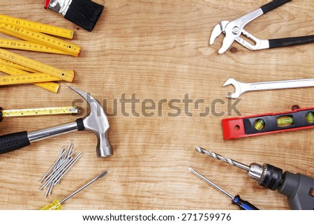 Assorted work tools on wood. Copy space - stock photo