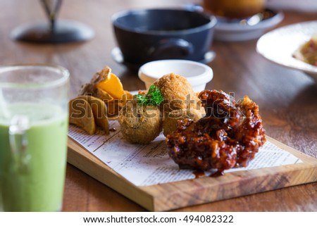 Assortment of appetizer on wooden table. Bitterballen, spicy fried chicken wings, fried potato wedges garnished with parsley