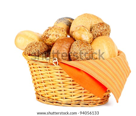Assortment of baked bread in a basket on white background - stock photo