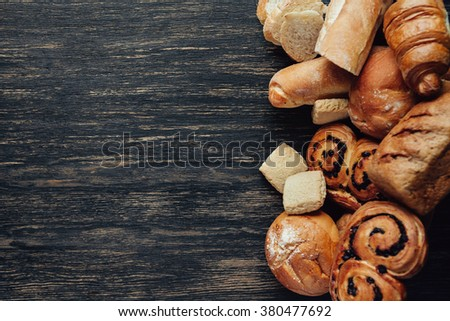 assortment of baked bread on black wood table. Top view with copy space - stock photo