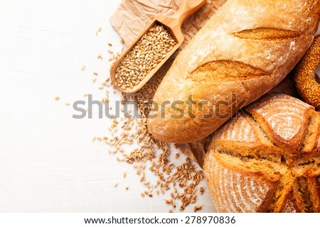 Assortment of baked bread on white wooden table background