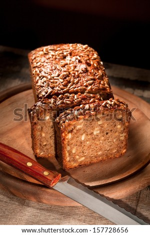 assortment of baked bread with seeds on wood table and black background