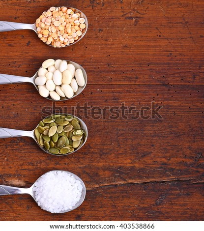 Assortment of beans and spices on old wooden table - stock photo