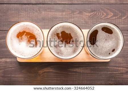 Assortment of beer glasses on a wooden background. Top view. - stock photo