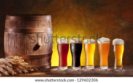 Assortment of beer glasses with a wooden barrel. Background - dark yellow gradient. - stock photo
