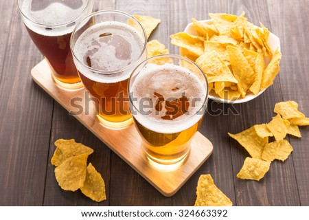 Assortment of beer glasses with nachos chips  on a wooden table. - stock photo