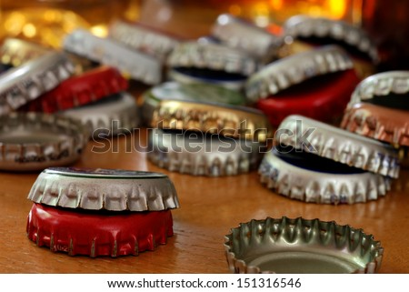 Assortment of bottle caps on wood bar with glasses of beer reflecting light in the background.  Macro with shallow dof. - stock photo