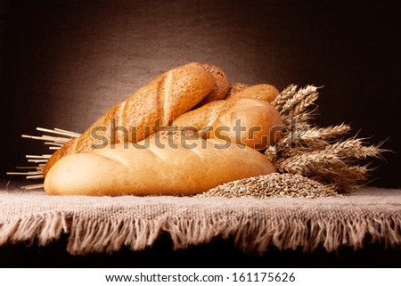 Assortment of breads and ears bunch still life on rustic background - stock photo