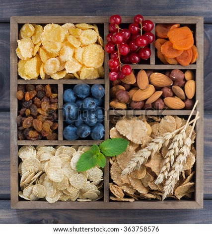 assortment of breakfast cereal, fruits, berries and nuts in a wooden box, top view, closeup - stock photo