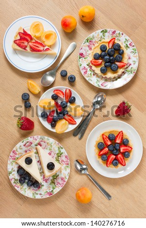 Assortment of cakes garnished with fresh berries on wooden table - stock photo